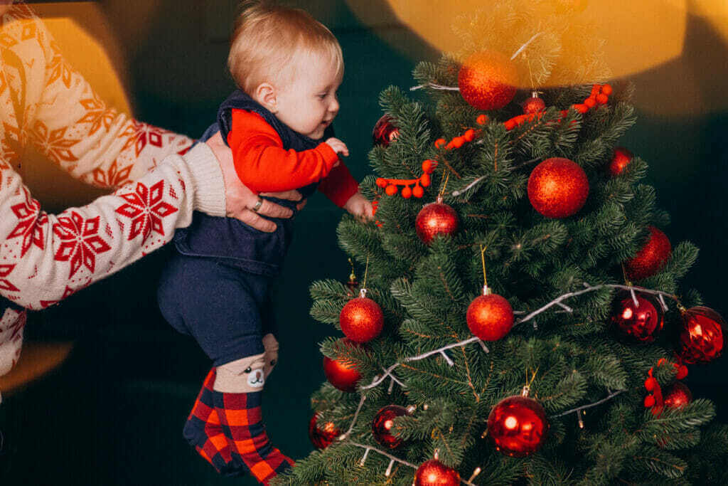 father with his baby daughter by christmas tree