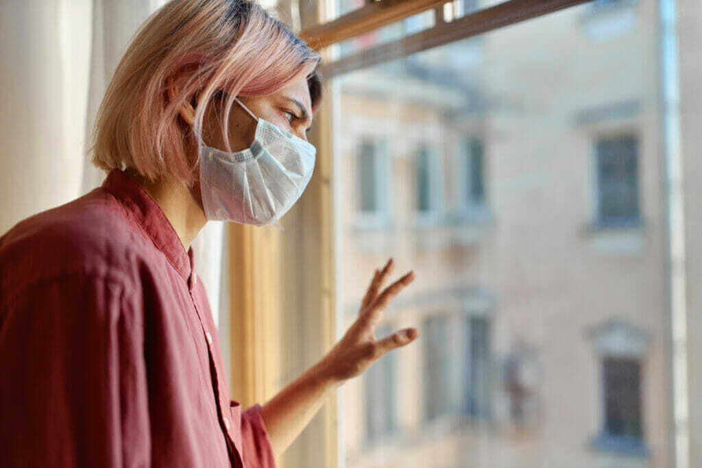 teenage girl with pinkish hair standing in front of closed window with hand on glass looking outside while staying at home during quarantine coronavirus pandemic and social distancing concept