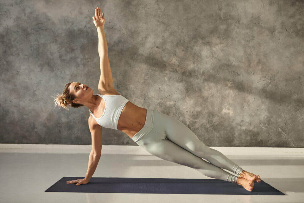 pretty girl wearing leggings and short top standing in side plank on one hand at gym training body core and balance strengthening abs muscles attractive female doing planking bodyweight exercise
