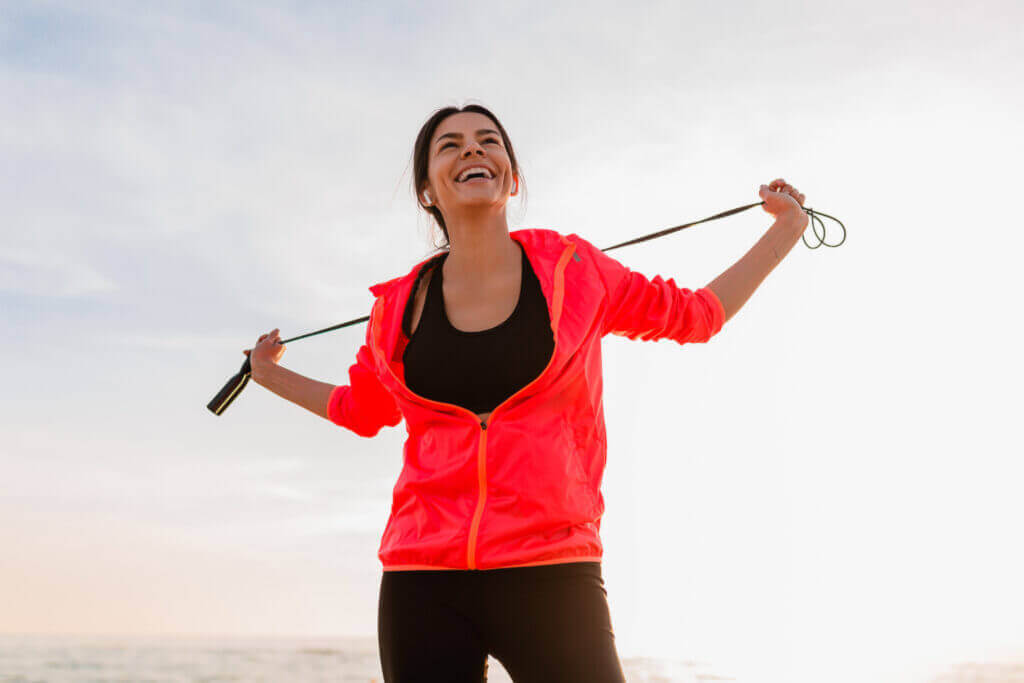 young attractive slim woman doing sport exercises morning sunrise sea beach sports wear healthy lifestyle listening music earphones wearing pink windbreaker jacket holding jump rope