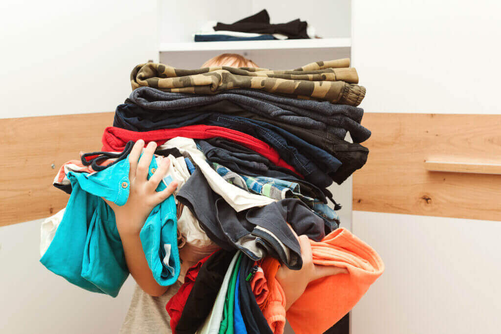 boy holding huge pile clothes kid makes order closet storage organization second hand kids clothes reusing reselling recycling donatation