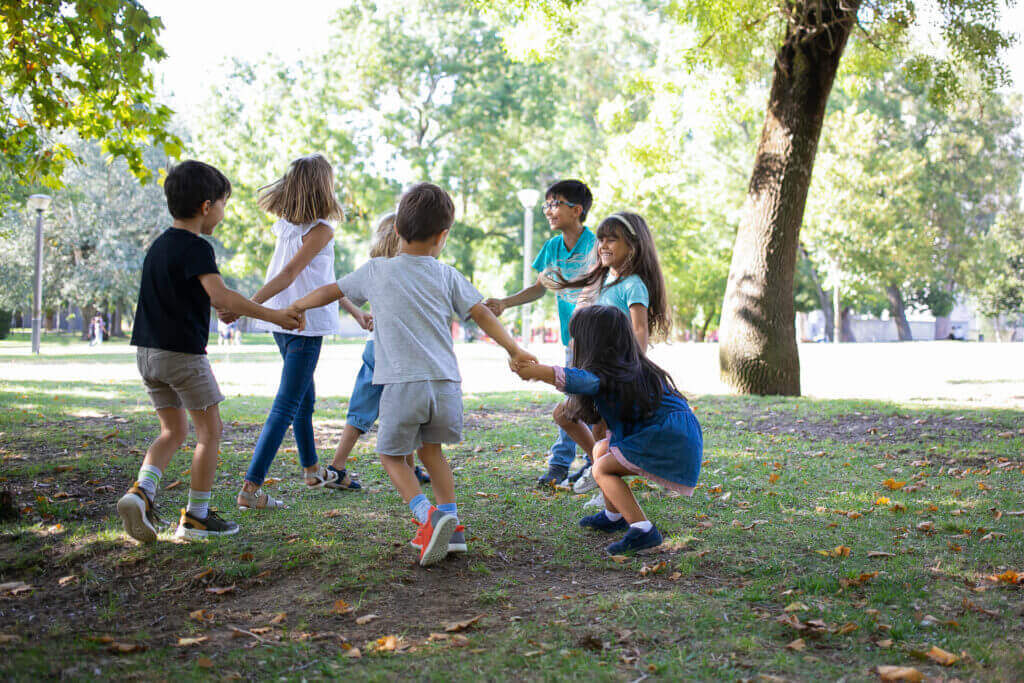 happy children playing together outdoors dancing around grass enjoying outdoor activities having fun park kids party friendship concept