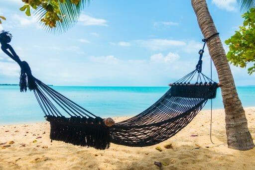 empty hammock swing around beach sea ocean with white cloud blue sky travel vacation
