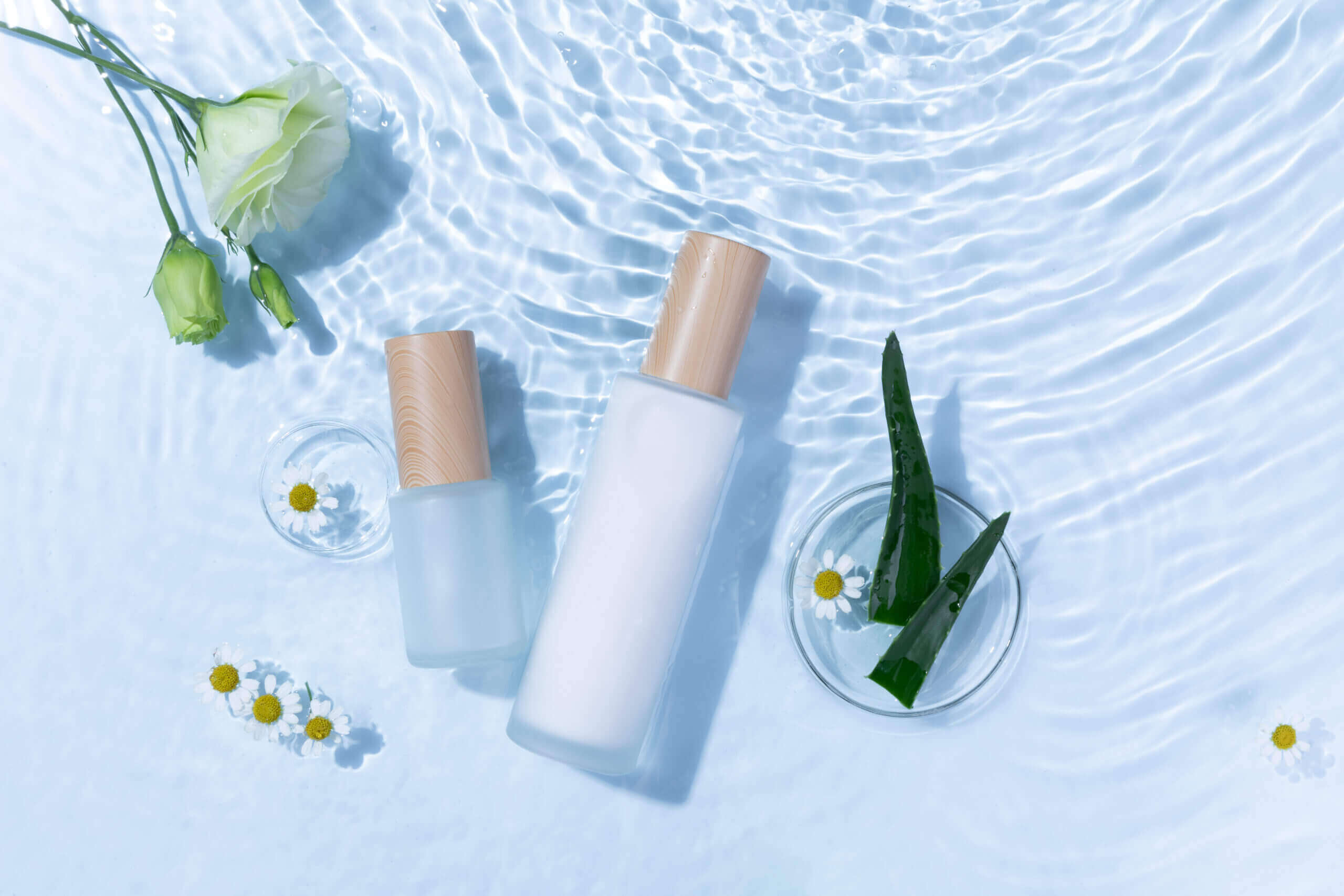 top view skincare bottles light blue water surface with aloe vera daisy flowers scaled